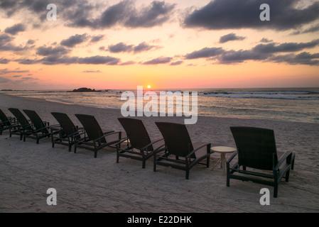 Coucher du soleil sur la plage avec chaises de plage à Punta Mita, au Mexique. Banque D'Images