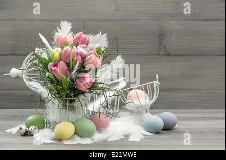 Composition de Pâques avec des oeufs et fleurs tulipes pastel nostalgique. home intérieur. retro photo couleur Banque D'Images