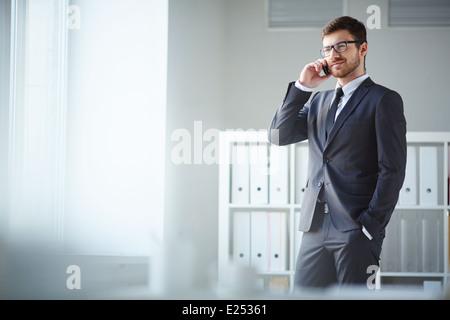 Handsome businessman en costume et lunettes parlant sur l'phone in office Banque D'Images