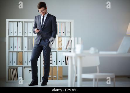 Handsome businessman en costume et lunettes écrit sms in office Banque D'Images
