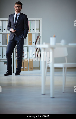 Handsome businessman en costume et lunettes looking at camera in office Banque D'Images
