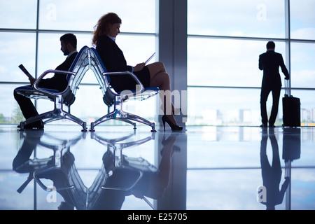 La lecture de deux de ses partenaires d'affaires à l'aéroport à l'arrière-plan de leur collègue avec valise par Banque D'Images