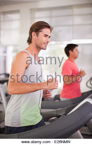 Smiling man running on treadmill in gymnasium Banque D'Images