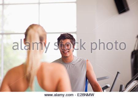 L'homme et la femme à parler sur des tapis roulants dans un gymnase Banque D'Images