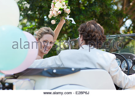 Bride and Groom riding in convertible Banque D'Images