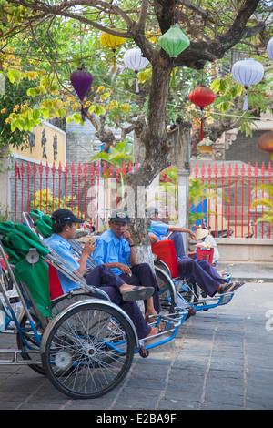 Les hommes assis dans cyclos, Hoi An (Site du patrimoine mondial de l'UNESCO), Quang Jambon, Vietnam Banque D'Images