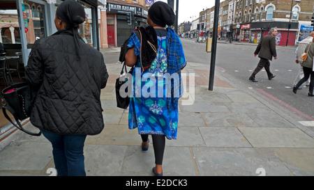 Vue arrière de l'Afro femme sur Kingsland Road Port d'impression textile africaine dans Dalston London E8 England Banque D'Images