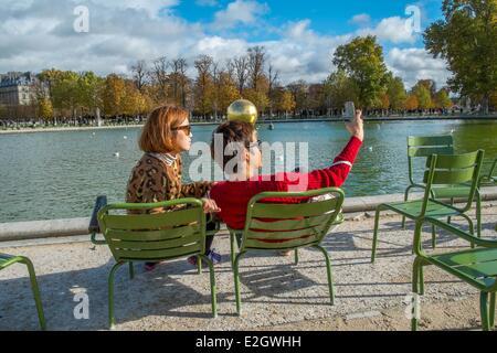 France Paris Les Jardins des Tuileries tourist couple photographing themselves en arrière-plan Sphère dorée illustration Banque D'Images