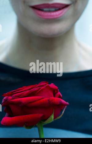 Femme tenant une rose, cropped Banque D'Images