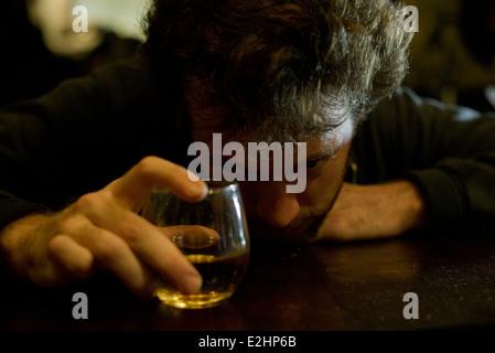 L'homme au bar avec un verre de whisky resting head on arms Banque D'Images