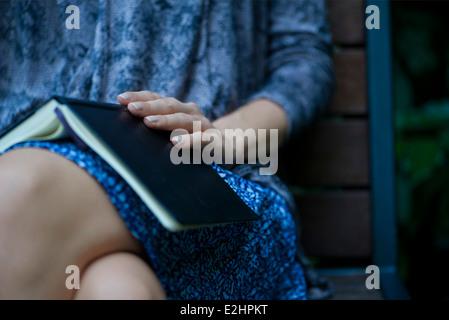 Femme assise avec livre ouvert reposant sur les genoux, cropped Banque D'Images