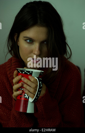 Woman in sweater holding mug, portrait Banque D'Images