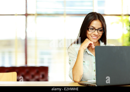 Smiling businesswoman travaillant sur le laptop at office