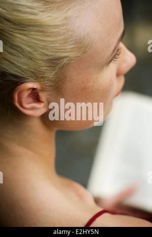 Woman looking away in thought lors de la lecture de livre, cropped Banque D'Images