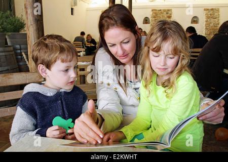 Une jeune femme lit un livre à deux jeunes enfants dans un restaurant à Cape Town Banque D'Images