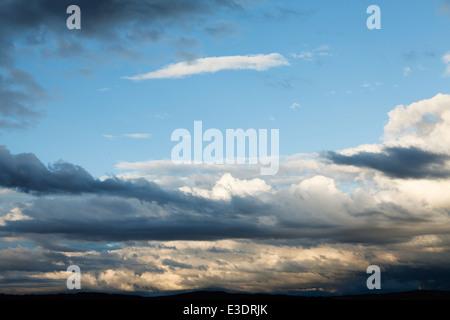 Les nuages duveteux gris dans le ciel bleu Banque D'Images