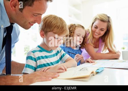 Les parents d'aider les enfants à faire leurs devoirs dans la cuisine Banque D'Images