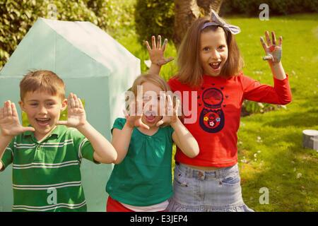 Enfants souriants avec les mains posées dans le jardin Banque D'Images