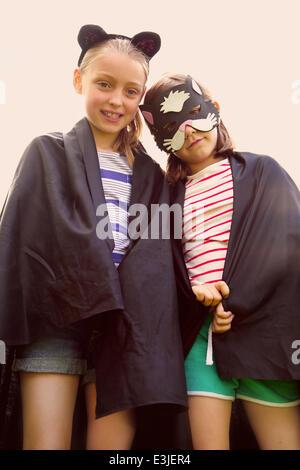 Les jeunes filles portant Cape et masque Banque D'Images
