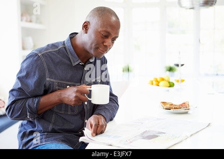 African American Man Eating Breakfast and Reading Newspaper Banque D'Images