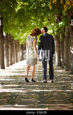 Couple en train de marcher sur la rue bordée d'tenant les mains, vue arrière Banque D'Images
