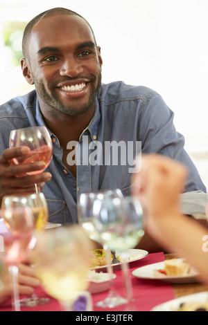 Young Man Relaxing At Dinner Party Banque D'Images