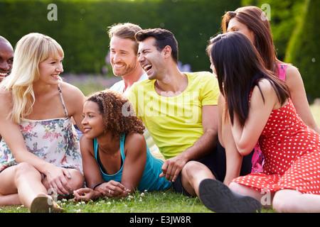 Groupe d'amis assis sur l'Herbe Ensemble Banque D'Images
