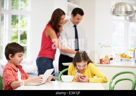 Les appareils numériques à l'aide de la famille à Table de Petit Déjeuner Banque D'Images