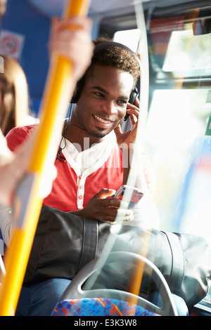 Man Wearing Headphones Listening to Music On Bus Banque D'Images