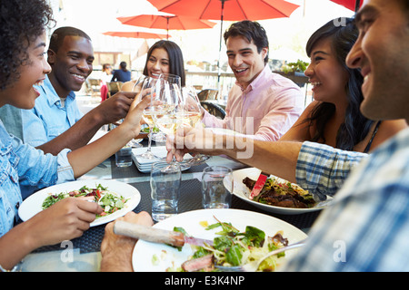 Group of Friends Enjoying Meal At Outdoor Restaurant Banque D'Images