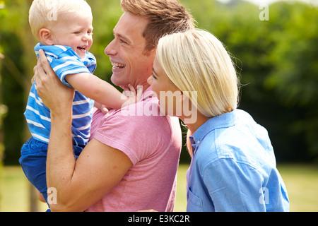 Les parents hugging jeune fils dans le jardin