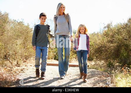 Mère et enfants Randonnées en campagne portant des sacs à dos Banque D'Images