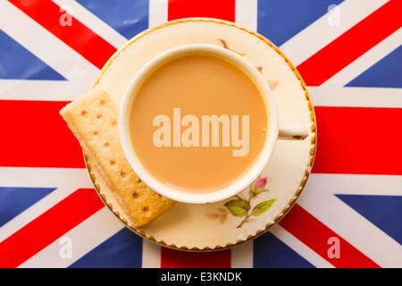 Une tasse de thé anglais traditionnel servi dans une tasse et soucoupe cina osseuse en haut d'un Union Jack flag Banque D'Images
