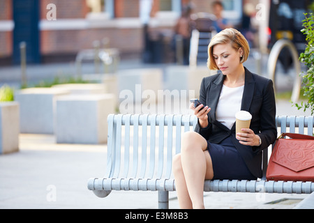 Businesswoman On Park Bench With Mobile Phone Café Banque D'Images