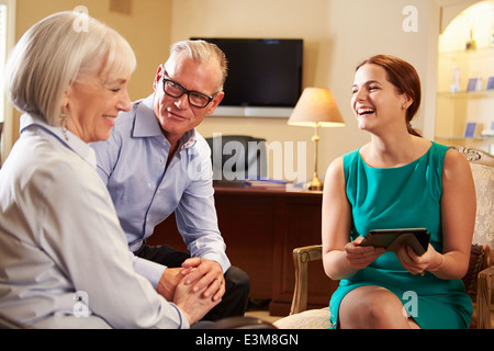 Vieux couple parler de conseiller financier à l'Office de Tourisme Banque D'Images
