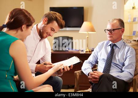 Jeune couple parlant à conseiller financier à l'Office de Tourisme Banque D'Images