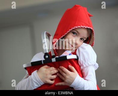 Jolie fille déguisée en Petit Chaperon Rouge (Rotkaeppchen) pendant un carnaval partie dans le jardin d'enfants. Banque D'Images