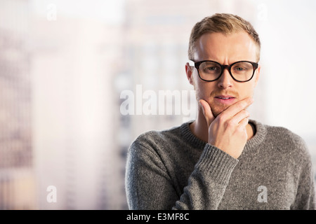 Pensive businessman with hand on chin Banque D'Images