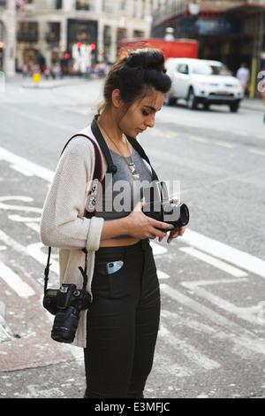 Jeune femme séduisante étudiant en photographie avec un appareil photo numérique Hasselblad et prendre des photos Banque D'Images