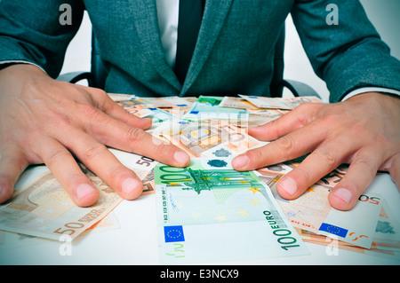 Man in suit assis dans un bureau plein de projets euro essayant de tenir eux illustrant la richesse ou de la gourmandise Banque D'Images
