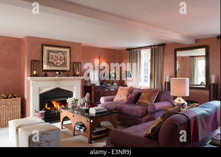 Table basse recouverte de marbre et de vache poufs design par Beckford dans la salle de séjour avec cheminée Banque D'Images