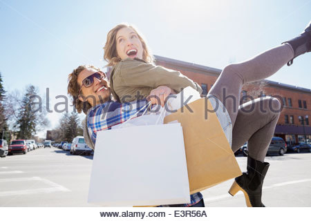 Playful couple on sunny urban street Banque D'Images