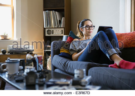 Woman using digital tablet on sofa Banque D'Images