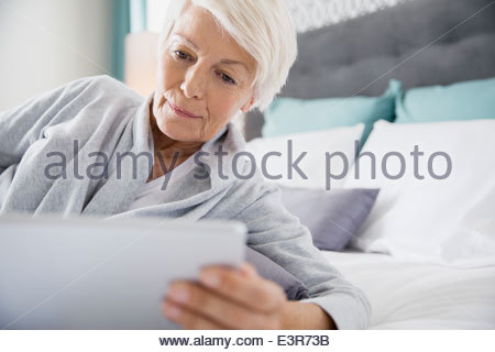 Woman using digital tablet in bed Banque D'Images