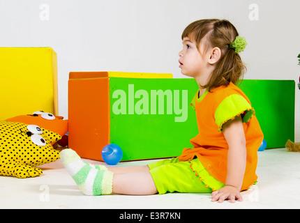 Petite fille européenne est assis parmi les jouets Banque D'Images