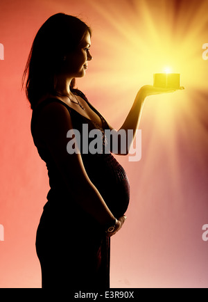 Silhouette of pregnant woman holding glowing don Banque D'Images