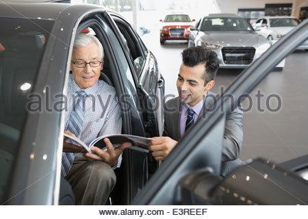 Vendeur et homme avec brochure en car showroom Banque D'Images
