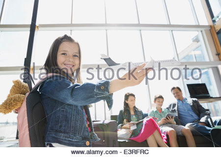 Girl Playing with toy airplane in airport Banque D'Images
