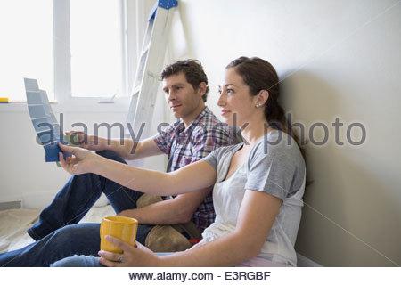 Couple drinking coffee et la visualisation d'échantillons de peinture Banque D'Images