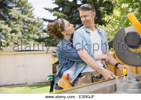 Couple hugging at scie de table in backyard Banque D'Images